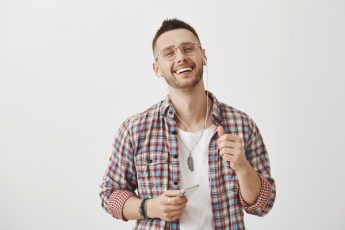 Guy checks out song of singer his friend suggested to listen. Cute slender man in glasses smiling with pleased expression, holding smartphone and wearing earphones, feeling satisfaction of good vibes.
